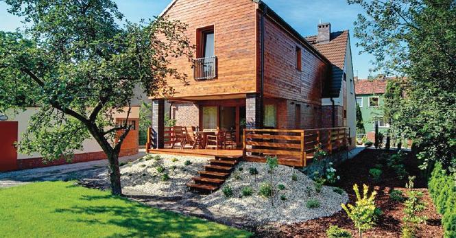 Część elewacji domu została wykończona okładziną drewnianą